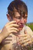 Boy has a shower at the beach — Stock Photo