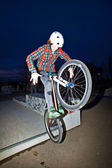 Boy on his dirtbike jumping at the skate park by night — Stock Photo