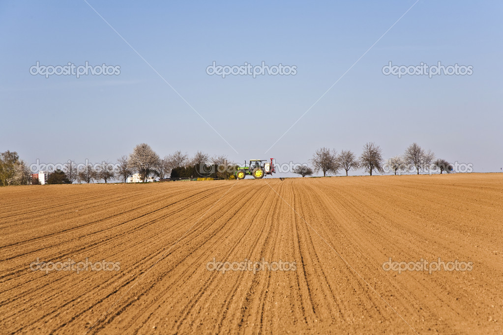 Freshly ploughed acre with tractor at the horizon — Stock Photo #5523862