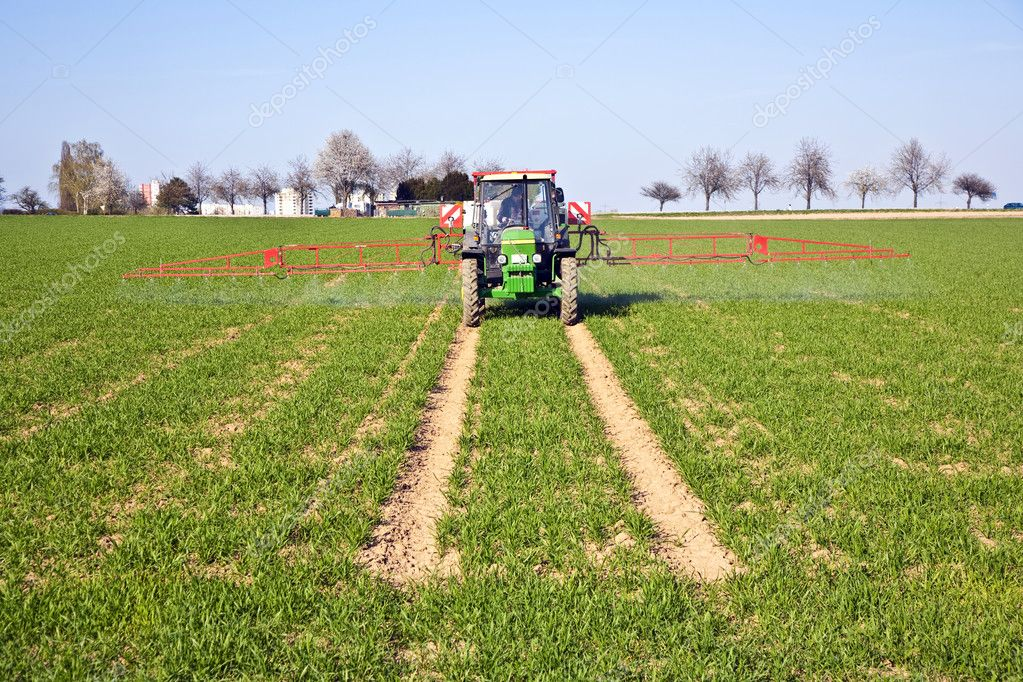 Tractor on field sputtering pest protection on plants — Stock Photo #5523879