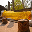 Lying Buddha dressed in yellow scarf in temple Wat Yai Chai-mong - Zdjęcie stockowe