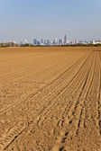 Freshly plowed field with cityscape of Frankfurt at the horizon — Stock Photo