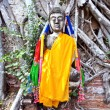Buddha covered by roots in temple area Wat Phra Si Sanphet - Stock Photo