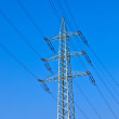 Electricity tower with power lines against a blue sky — Stock Photo #5551489