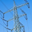 Electricity tower with power lines against a blue sky — Stock Photo #5551702