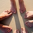Feet of a family in the fine sand of the beached, grouped in a c — Stock Photo