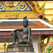 Sitting man on a stone capital in the Grand Palace, Bangkok - Stock Photo
