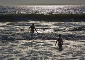 Bathing in sunset in waves at the beach — Stock Photo