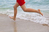 Feet of boy running along the beach — 图库照片