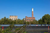 Old abandoned industrial building at the river with ship — Stock Photo