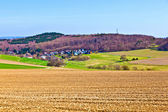 Landscape with fields and a village with hills at the horizon — Stock Photo