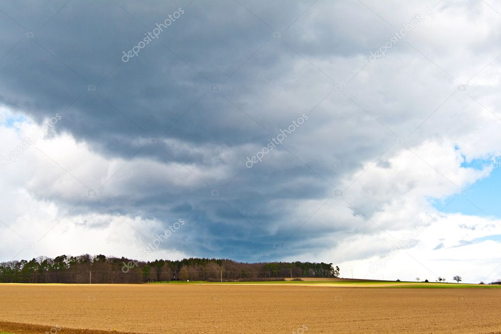 Dark clouds and blue sky over fields  Stock Photo #5616431
