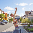 Boy riding skateboard going airborne at sidewalk — Stock Photo #5628793