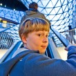 Child on moving staircase looks self confident — Stock Photo