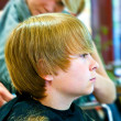 Smiling young boy  at the hairdresser - Stock Photo