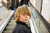 Child is smiling confident on a stairway in a shopping mall — Stock Photo