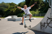 Boy rides scooter in a skate park — Stock Photo