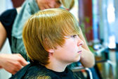 Smiling young boy at the hairdresser — Stock Photo
