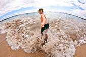 Chico tiene diversión en la playa de las olas — Foto de Stock