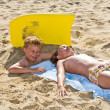 Boy and girl playing at the beach digging in the sand — Stock Photo