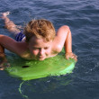 Stock Photo: Young boy is surfing in the ocean