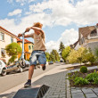 Boy riding a scooter going airborne — Stock Photo