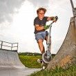 Boy rides scooter in the halfpipe — Stock Photo