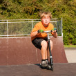 Boy rides scooter at the skate park - 