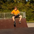 Boy rides scooter at the skate park — Foto Stock
