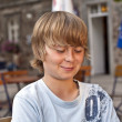 Portrait of happy smiling boy sitting in an outdoor restaurant — Stock Photo #5656645