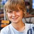 Portrait of happy smiling boy sitting in an outdoor restaurant — Stock Photo