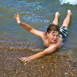 Boy lying in water gives hand sign — Stock Photo #5656863