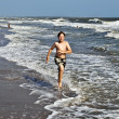 Young boy running through the water at the beach — Stock Photo #5656870