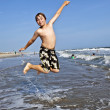 Jumping boy enjoys the beautiful ocean — Stock Photo #5656876