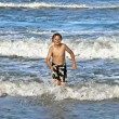 Young boy running through the water at the beach — Stock Photo #5656893