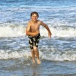 Young boy running through the water at the beach — Stock Photo #5656894
