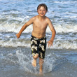 Young boy running through the water at the beach — Stock Photo #5656895