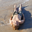 Boy lying at the beach and enjoying the ocean — Stock Photo #5656899