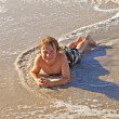 Boy lying at the beach and enjoying the ocean — Stock Photo #5656903