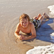 Boy lying at the beach and enjoying the ocean — Stock Photo #5656904