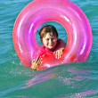 Boy in a swim ring has fun in the ocea — Stock Photo #5656954