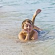 Boy enjoys lying at the beach in the surf — Stock Photo #5656996