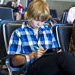 Boy is waiting for departure at the airport - Stock Photo