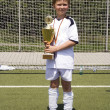 Young boy in soccer dress presents proud the cup — Stock Photo #5657188