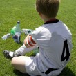 Exausted boy takes a rest in the halftime of a football match — Stock Photo