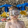 Child, boy with diving goggles is playing intensively at the sandy beach — Foto de Stock
