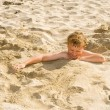Stock Photo: Boy is digging oneself into sandy beach and has lot of fun