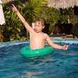 Young boy in a floting tyre enjoys fresh water in the pool — Photo