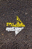 Arrow in yellow and white on a paveway for orientation — Stock Photo