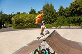 Boy is jumping with a scooter over a spine in the skate parc and — Stock Photo
